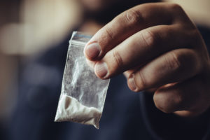 close up of hand holding a small plastic packet containing white powdered substance